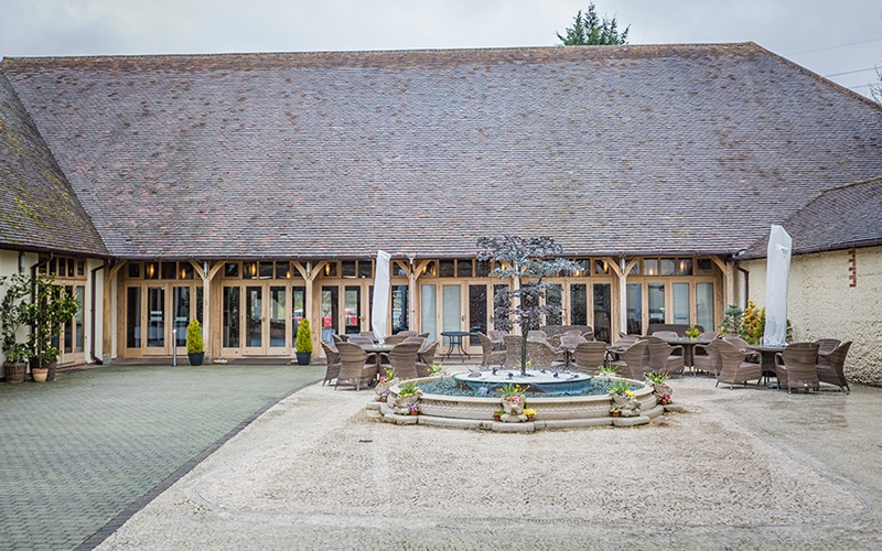 Rivervale Barn is one of the finest wedding venues in Hampshire. Enjoy the venue's courtyard with water feature and outdoor seating area.