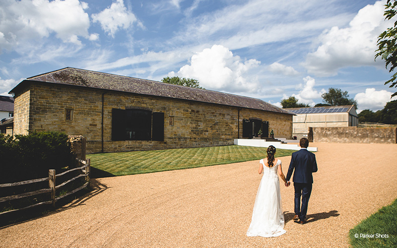 A happy couple taking a moment at Hendall Manor Barn wedding venue in East Sussex | CHWV