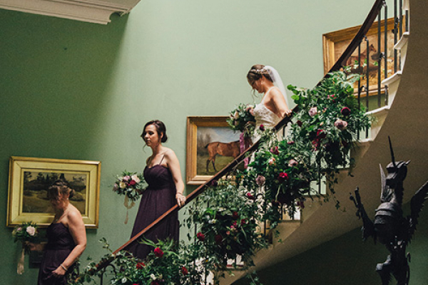 A bride and bridesmaids on the staircase at Burton Court wedding venue in Herefordshire | CHWV