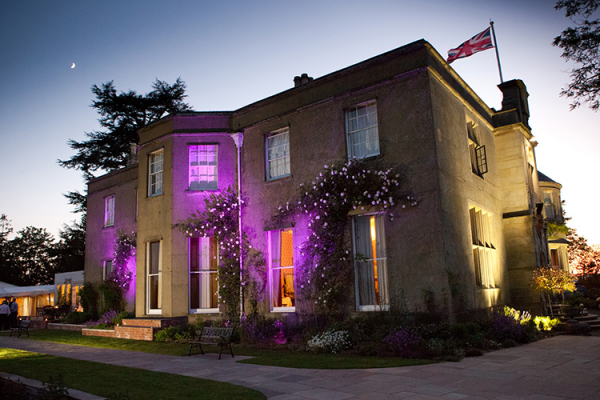 The house lit up in the evening at Burton Court wedding venue in Herefordshire | CHWV