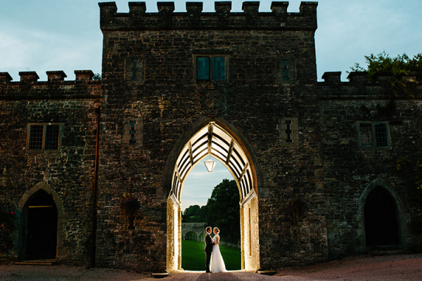 A couple taking a moment under the archway at Clearwell Castle wedding venue in Gloucestershire | CHWV