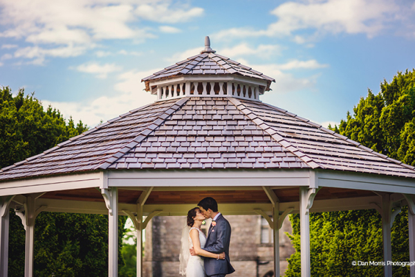 A couple take a moment under the bandstand at Clearwell Castle wedding venue in Gloucestershire | CHWV