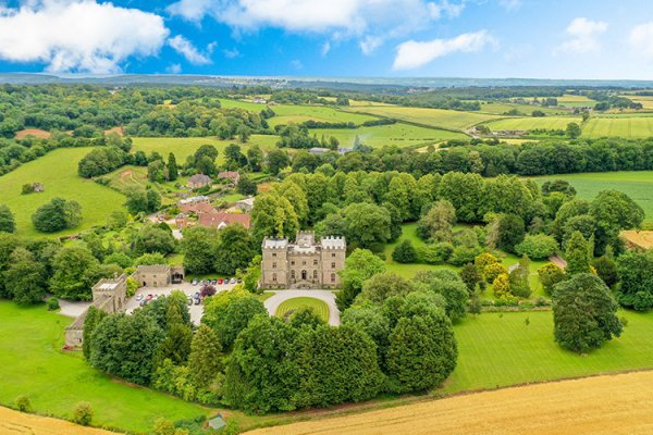 An aerial view of the castle and beautiful grounds at Clearwell Castle wedding venue in Gloucestershire | CHWV