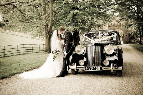 A couple take a moment by their wedding car at Clearwell Castle wedding venue in Gloucestershire | CHWV