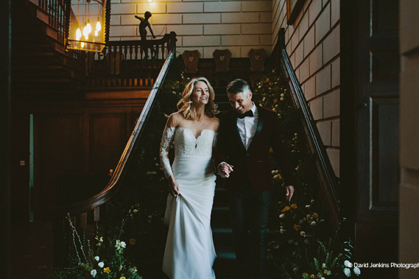A happy couple in front of the staircase at Davenport House country house wedding venue in Shropshire | CHWV