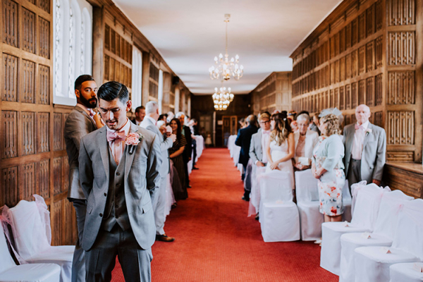 A groom waiting for his bride at Gosfield Hall wedding venue in Essex | CHWV