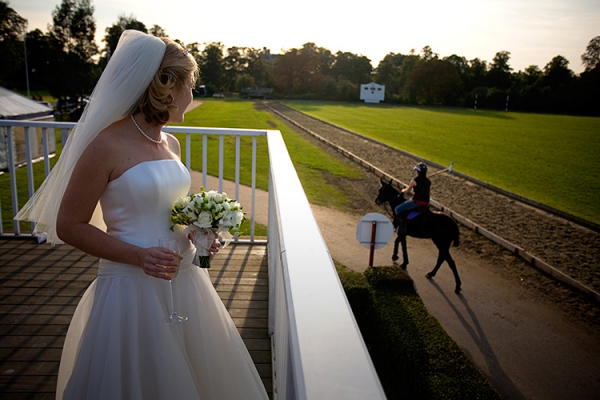 A bride looking out over the polo field at Ham Polo Club