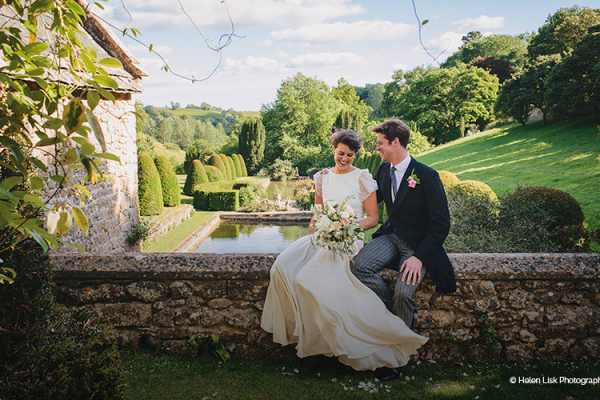 Bride and Groom sitting on the wall outside Mapperton - Marquee Wedding Venue in Dorset