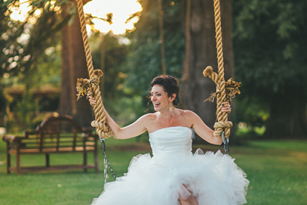 The bride on the swing in the garden of Maunsel House - Country House Wedding Venue in Somerset