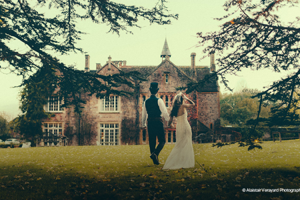 Bride and groom strolling across the lawn towards Maunsel House - Country House Wedding Venue in Somerset