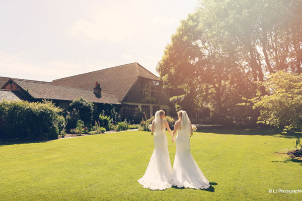 Rivervale Barn wedding venue provides a stunning backdrop to your wedding pictures. Here the wedding couple walk hand in hand