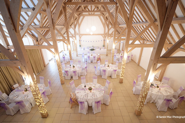 The Dining Barn looks beautiful with purple ribbon and chair covers as part of the wedding decorations.