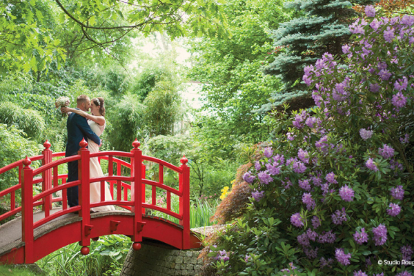 A happy couple cuddle on the red Japanese bridge surrounded by colourful flowers and trees in full bloom.