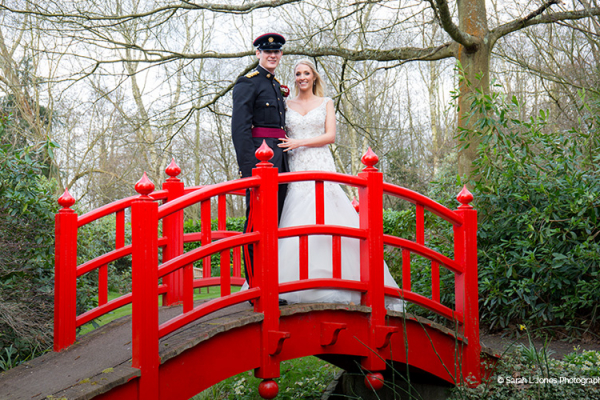 A happy couple poses on the striking red Japanese bridge in the gardens.