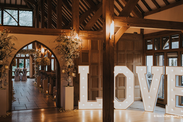 Set for romantic winter wedding, huge light-up letter spell the word love outside the ceremony barn.