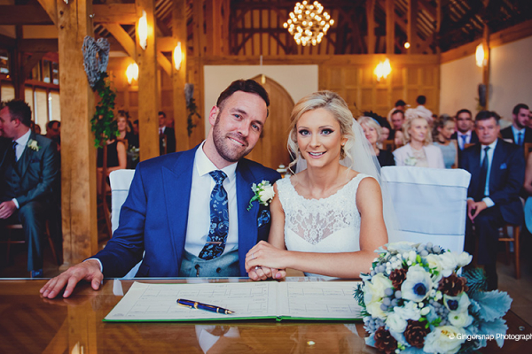 The happy couple sign the registrar in the Ceremony Barn at one of the finest Hampshire wedding venues.