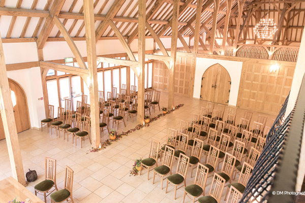 Light floods into the Ceremony Barn through its floor to ceiling glass windows. Chairs are lined neatly in rows.
