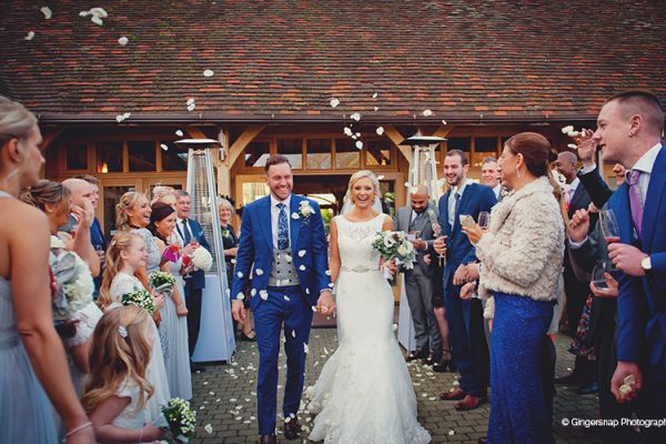 Guests line themselves either side of the couple ready to throw confetti at the happy couple.