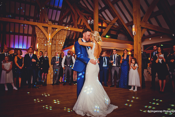 The happy couple enjoy their first wedding dance on the dance floor underneath romantic lighting.