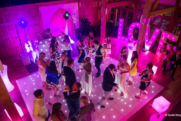 The venue's dance area lights up with pink lighting and guests dancing on a black and white dance floor - party wedding venue.