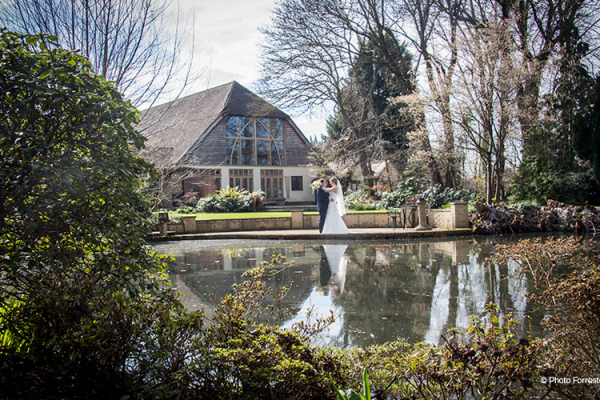 A happy couple stand by the barn wedding venue's pond for wedding pictures - winter wedding.