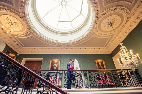 A bride and grrom on the staircase at Addington Palace in Surrey | CHWV