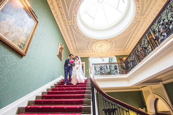 Happy couple taking a moment on the staircase at Addington Palace wedding venue in Surrey | CHWV
