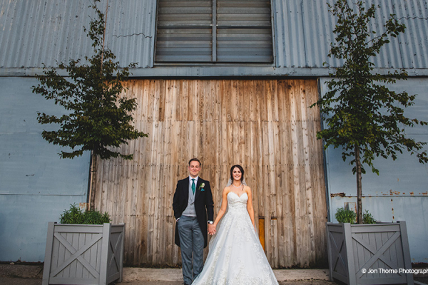 A happy couple pose outside the barn at Alrewas Hayes wedding venue in Staffordshire | CHWV