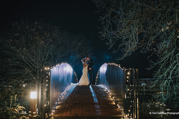 A couple taking a moment on the bridge at Bassmead Manor Barns wedding venue in Cambridgeshire | CHWV