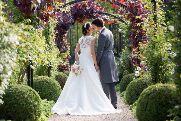 A happy couple in the beautiful gardens at Braxted Park in Essex | CHWV