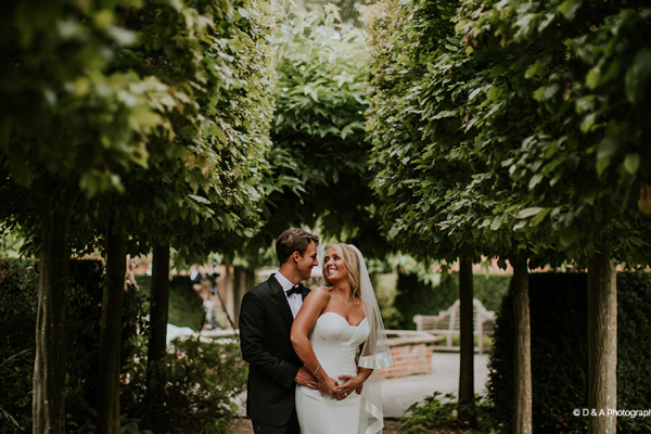 A happy couple in the beautiful grounds at Braxted Park country house wedding venue in Essex | CHWV