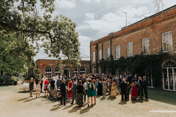 Guests gather for a drinks reception at Braxted Park wedding venue in Essex | CHWV