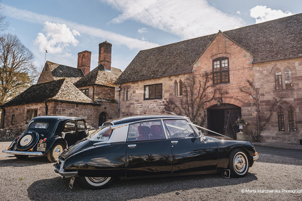 Vintage cars in the courtyard at Brinsop Court country house wedding venue in Herefordshire | CHWV