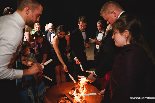 Toasting marshmallows in a firepit at Brinsop Court country house wedding venue in Herefordshire | CHWV