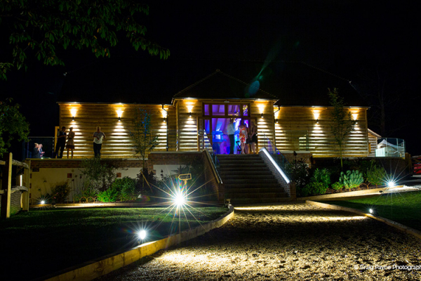 Brookfield Barn wedding venue in West Sussex lit up in the evening | CHWV