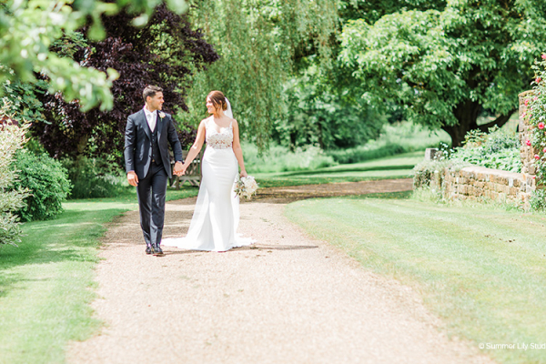 A happy couple taking a moment in the beautiful gardens at Crockwell Farm wedding venue in Northamptonshire | CHWV