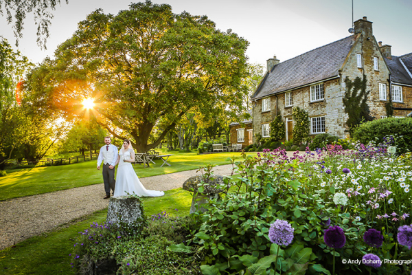 A happy couple take a stroll at sunset at Crockwell Farm wedding venue in Northamptonshire | CHWV