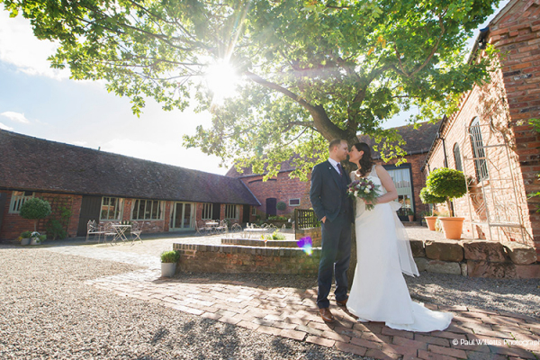 A happy couple in the courtyard at Curradine Barns wedding venue in Worcestershire | CHWV