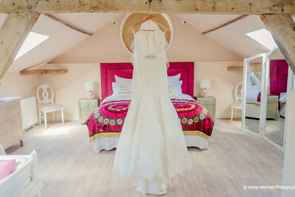 Brides dress hanging in the honeymoon suite at Gaynes Park barn wedding venue in Essex | CHWV