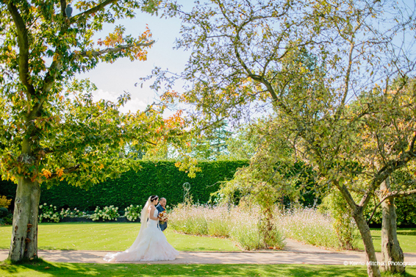 A bride walking down the Garden Aisle with her father at Gaynes Park barn wedding venue in Essex | CHWV