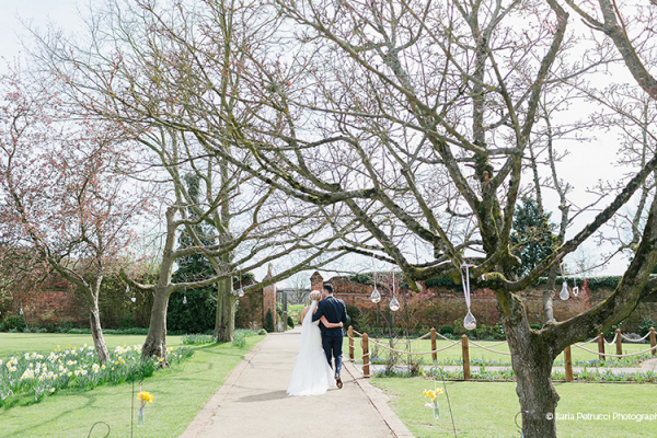 A happy couple taking a stroll in the gardens at Gaynes Park barn wedding venue in Essex | CHWV