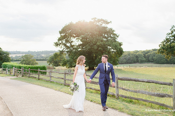 A happy couple taking a stroll in the beautiful grounds at Gaynes Park barn wedding venue in Essex | CHWV