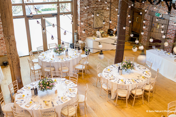 Set up for a wedding breakfast in The Mill Barn at Gaynes Park barn wedding venue in Essex | CHWV