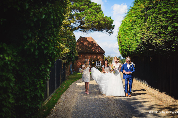Bridal party walking from Apple Loft Cottage at Gaynes Park barn wedding venue in Essex | CHWV