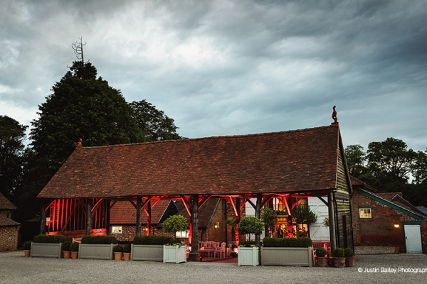 The Gather Barn lit up in the evening at Gaynes Park barn wedding venue in Essex | CHWV