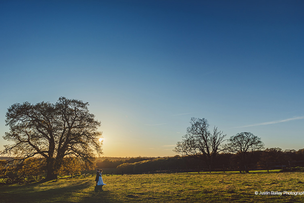 A happy couple in the beautifyl grounds at Gaynes Park barn wedding venue in Essex | CHWV