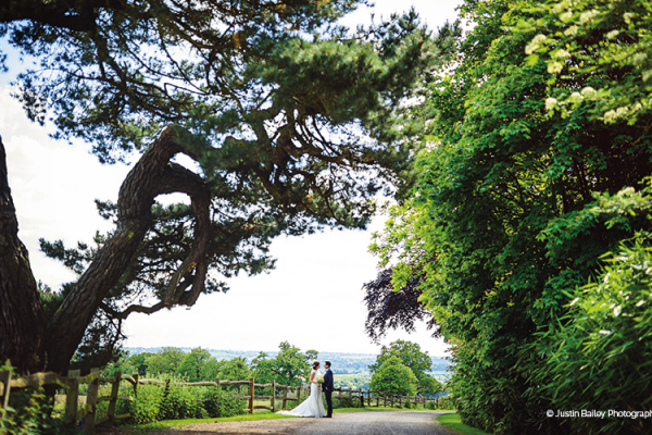 A happy couple in the beautiful grounds at Gaynes Park barn wedding venue in Essex | CHWV
