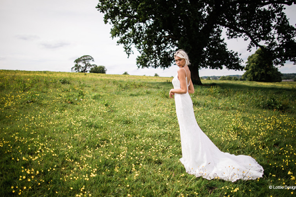 A bride taking a moment in the beautiful gardens at Gisburne Park Estate marquee wedding venue in Lancashire | CHWV