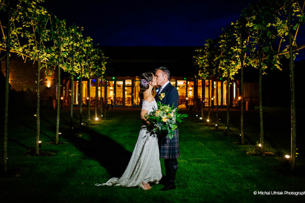 A happy couple in the beautiful grounds in the evening at Hazel Gap Barn wedding venue in Nottinghamshire | CHWV
