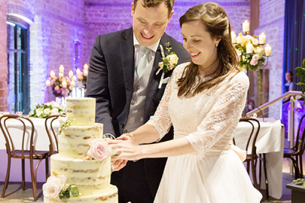 Bride and groom cutting their cake at Hendall Manor Barn wedding venue in East Sussex | CHWV